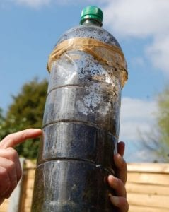 Plastic bottle filled with soil for composting