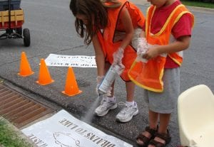 Kids painting a No Dump stencil on a storm drain