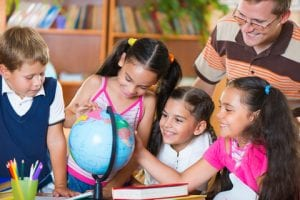 Young students looking at globe with their teacher