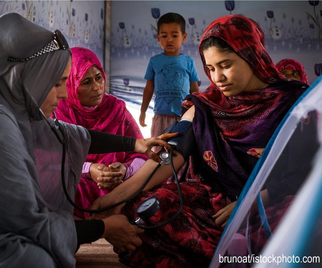 An Algerian woman measures the blood pressure of a woman who has recently given birth.