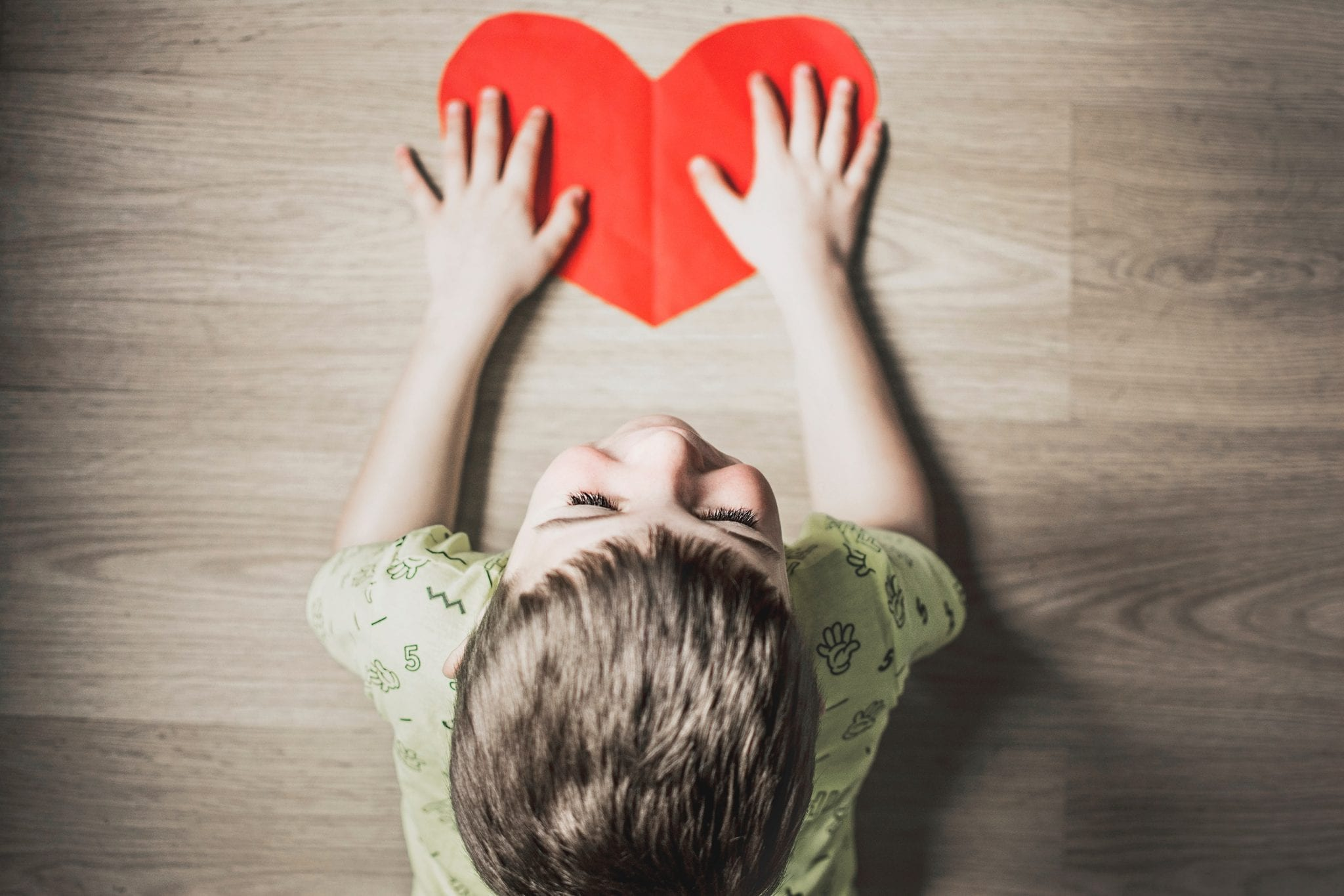 Young smiling child with hands on a paper heart