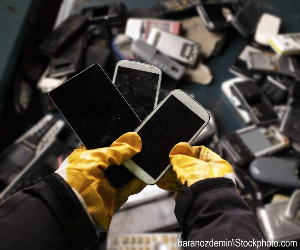 A worker holding cell phones and other electronics, e-waste ready to be recycled.