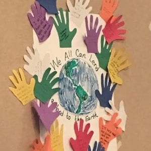 Handprints with environmental goals written on them