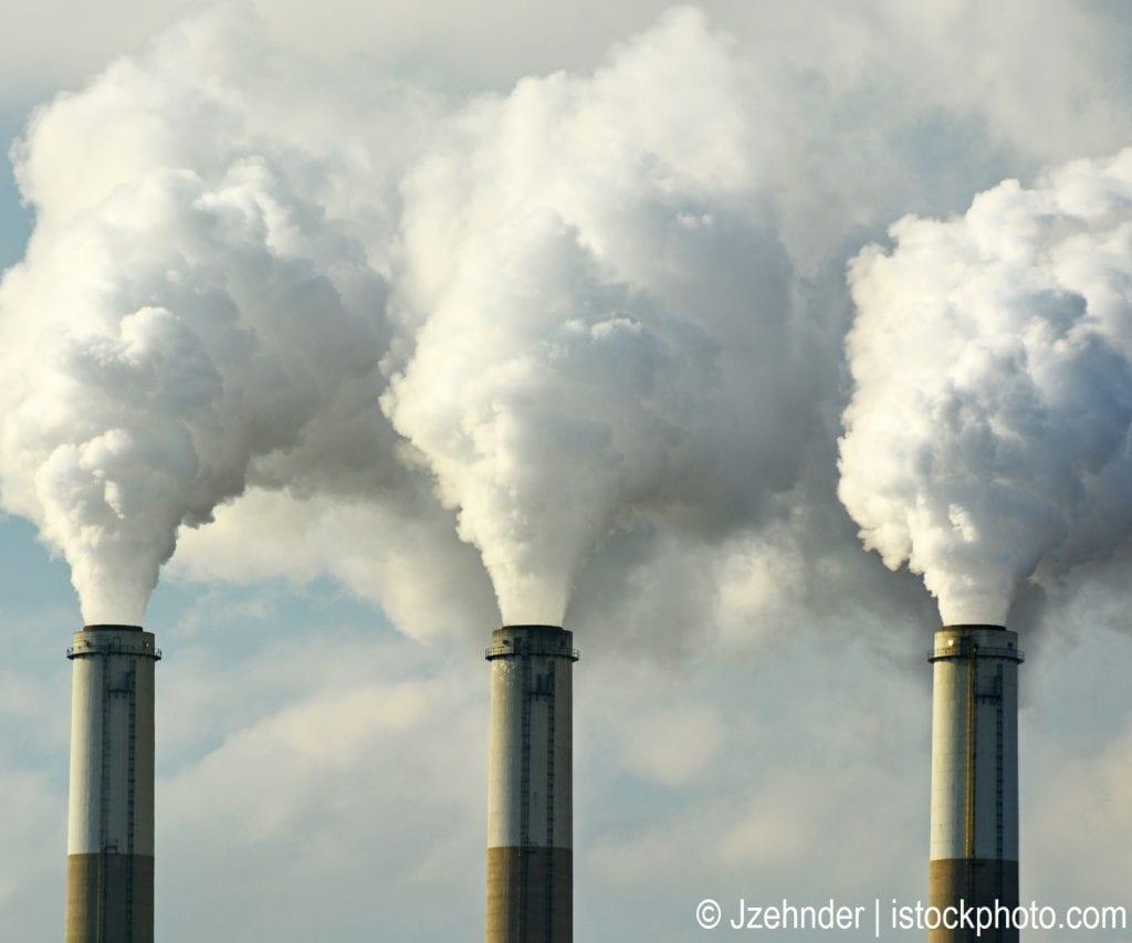 Smoke stacks at a power plant emitting smoke, a major source of air pollution.