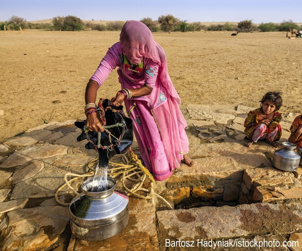 An Indian woman drawing water from a well while her children wait beside her.