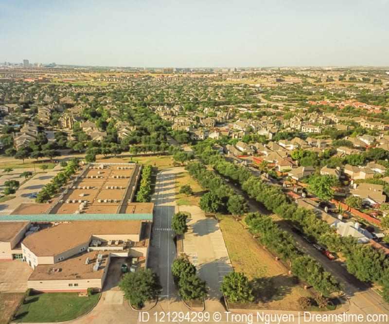 Aerial view of Irving, Texas shows green space among school, homes and roads.