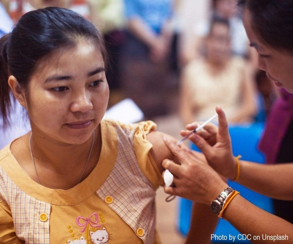 Woman receiving vaccine from nurse