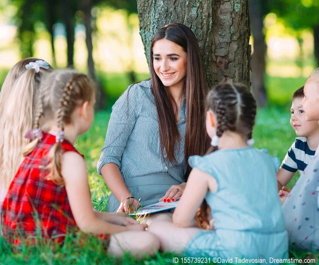 Teachers reads the book The Lorax to young students sitting outside near a tree