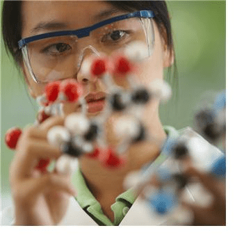 A woman in a lab coat and safety goggles examines a scientific object