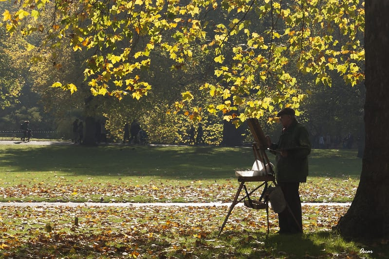 Elderly man painting on easel in park