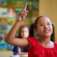 Elementary student raises hand and waits her turn to speak