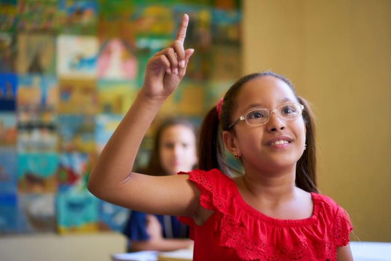 Elementary student raises hand and waits her turn to speak