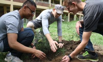 Three teens planting tree