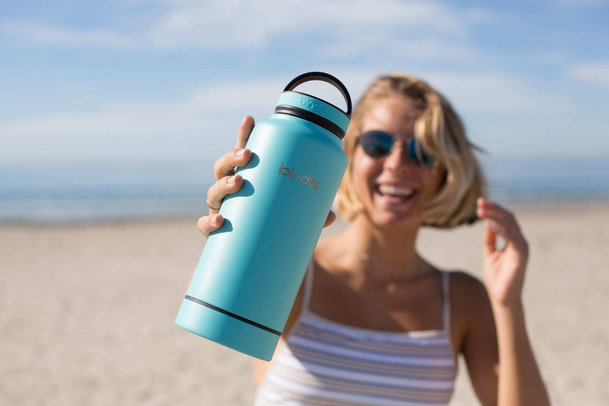 Woman on beach smiling and showing off blue, reusable water bottle