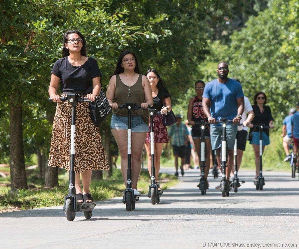 People ride e-scooters, a new means of transportation in the United States today