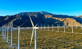 White wind turbines on brown sand with mountains in background
