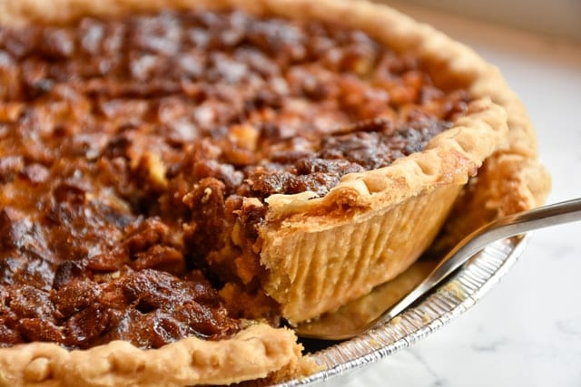 Close up view of a slice of pumpkin pie being removed by a fork