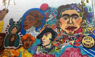 Colorful mural on white wall shows empowering paintings of Black and Brown women like Mary Church Terrell and Frida Khalo