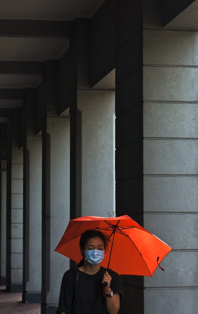 Woman in black shirt walks by columns while wearing a medical mask and holding an orange umbrella