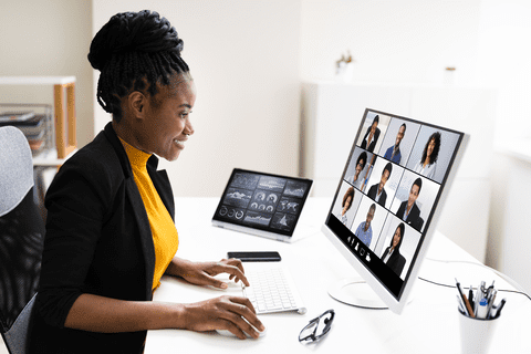 Woman sits at office desk and smiles at computer screen while on video conference call