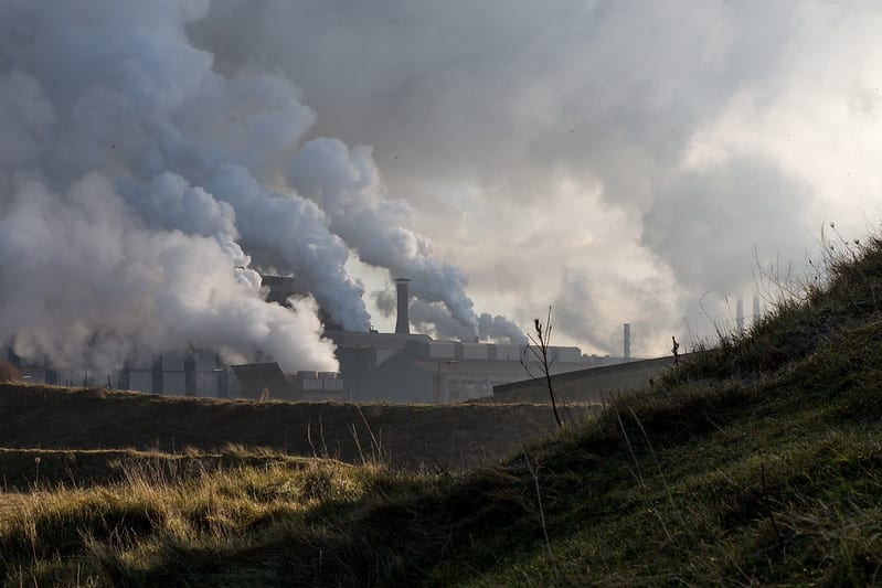 Factories behind grassy hills billow clouds of smoke that cover the sky