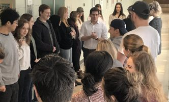 Students at King's University stand in a circle while a facilitator talks them through a demonstration of the Population Circle activity.